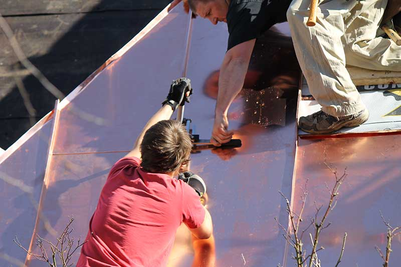 Metal roofing contractor working on new roof installation